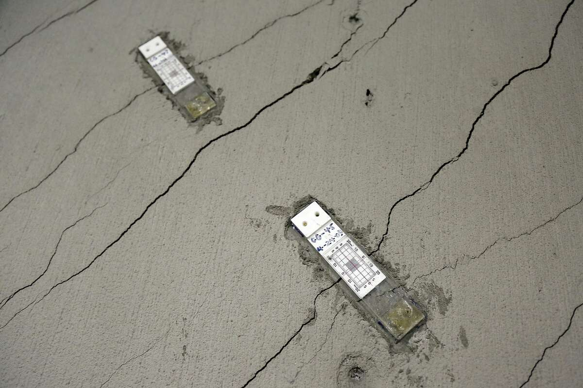 Stress gauges are placed along a wall with floor-to-ceiling cracks in the parking garage of the Millennium Tower in San Francisco.