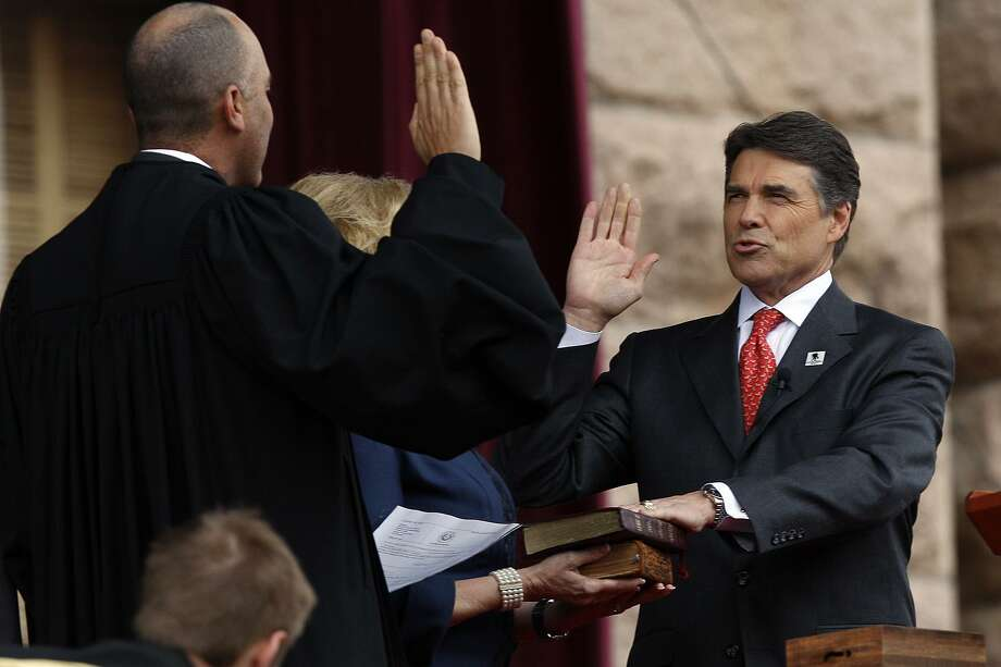 Texas Governor Rick Perry, right, is sworn-in by Supreme Court of Texas Chief Justice Wallace B. Jefferson during the 2011 Texas Inauguration Oath of Office Ceremony on the South Steps of the Texas Capitol in Austin, Tuesday, Jan. 18, 2011. It is Perry's fourth oath ceremony and Lt. Gov. David Dewhurst took the oath for a third term. Photo: JERRY LARA, STAFF / San Antonio Express-News / glara@express-news.net