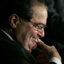 U.S. Supreme Court Justice Antonin Scalia smiles at the humorous comments of Supreme Justice John Paul Stevens. not seen, towards Scalia during the Seventh Circuit Court of Appeals annual dinner in Chicago, Monday, May 19, 2008. (AP Photo/Charles Rex Arbogast)