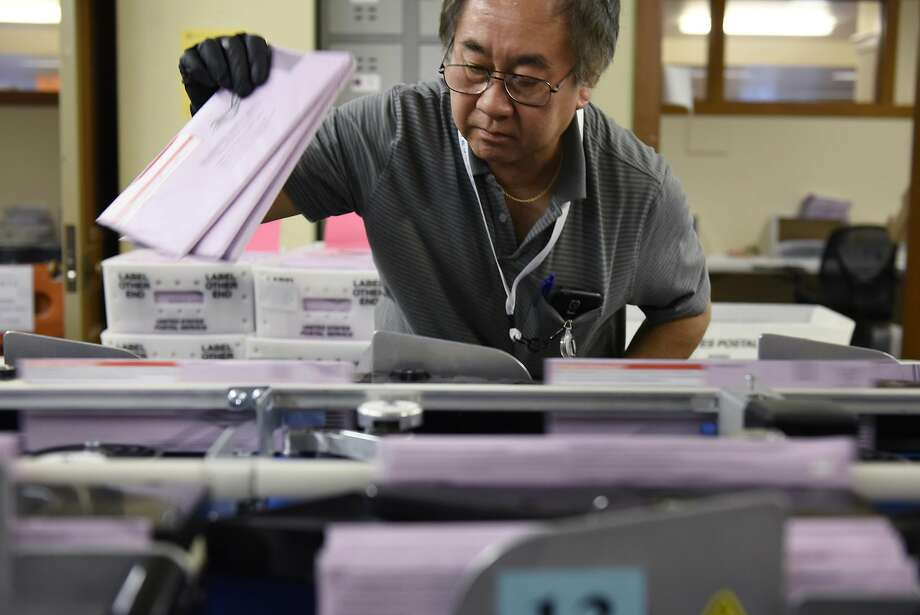 Election clerk Long Huang pulls mail-in ballots from a sorting machine at San Francisco City Hall on Wednesday. Photo: Michael Short, Special To The Chronicle