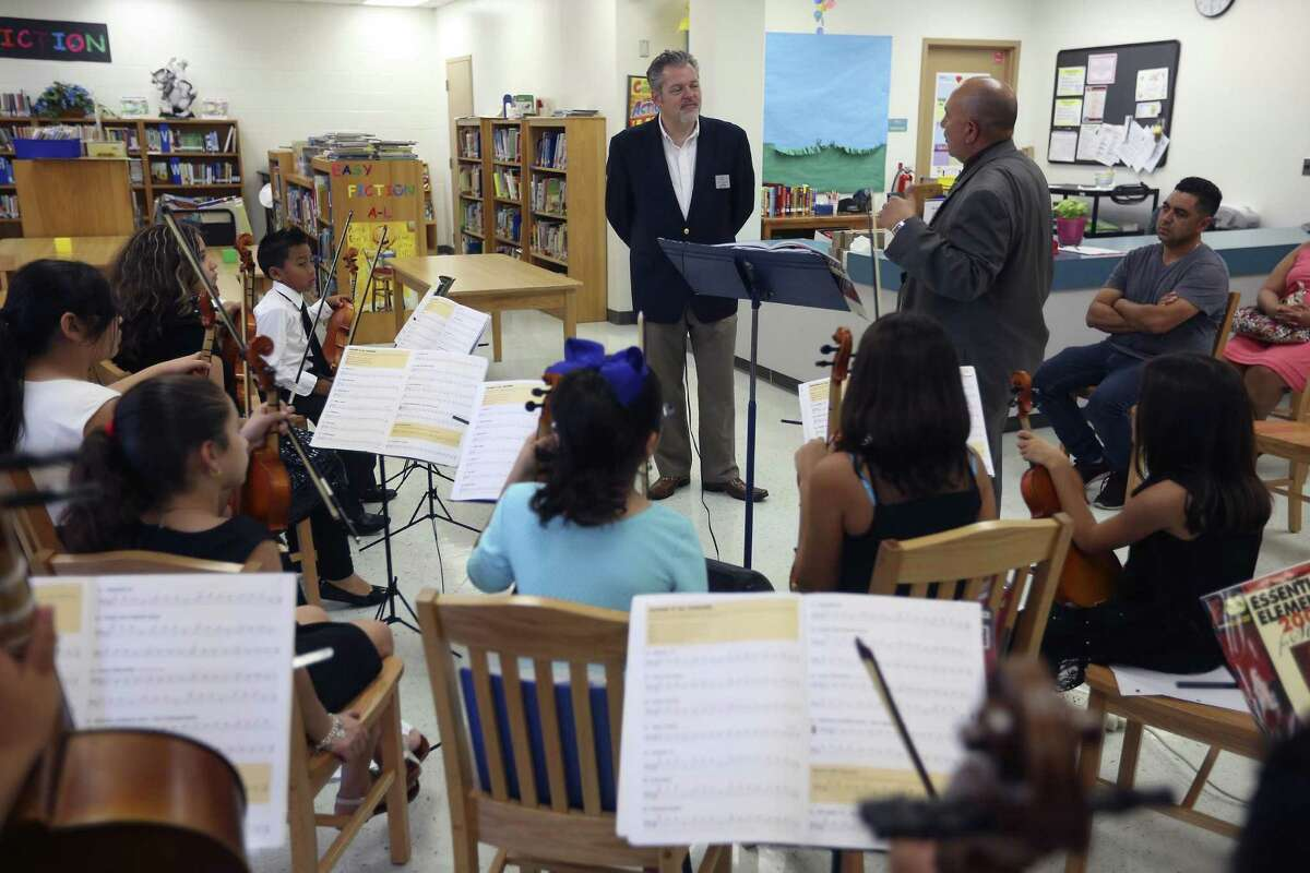 Troy Peters, standing at left, Music Director of YOSA (Youth Orchestras of San Antonio), talks with Winston Elementary School strings teacher Joe Vasquez, standing at right, Wednesday afternoon, Nov. 2, 2016 about the donation of instruments the youth orchestra was able to make to Winston students. After the brief words, Winston students played some songs for Peters.