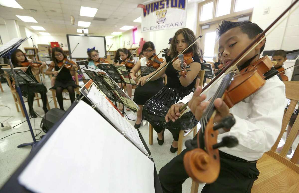 Winston Elementary School student Albert Arzola (right) plays violin with schoolmates during a brief event to thank the Youth Orchestras of San Antonio for nonprofit's recent donation of instruments to Winston.