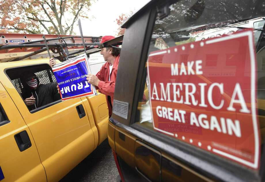 Former Connecticut gubernatorial candidate Joe Visconti hands several Donald Trump lawn signs to passersby while stumping for Trump in downtown Greenwich, Conn. Thursday, Nov. 3, 2016. Visconti rallied together a group of a dozen Trump supporters to gauge voter support and pass out Trump swag to passersby on the street. Photo: Tyler Sizemore / Hearst Connecticut Media / Greenwich Time