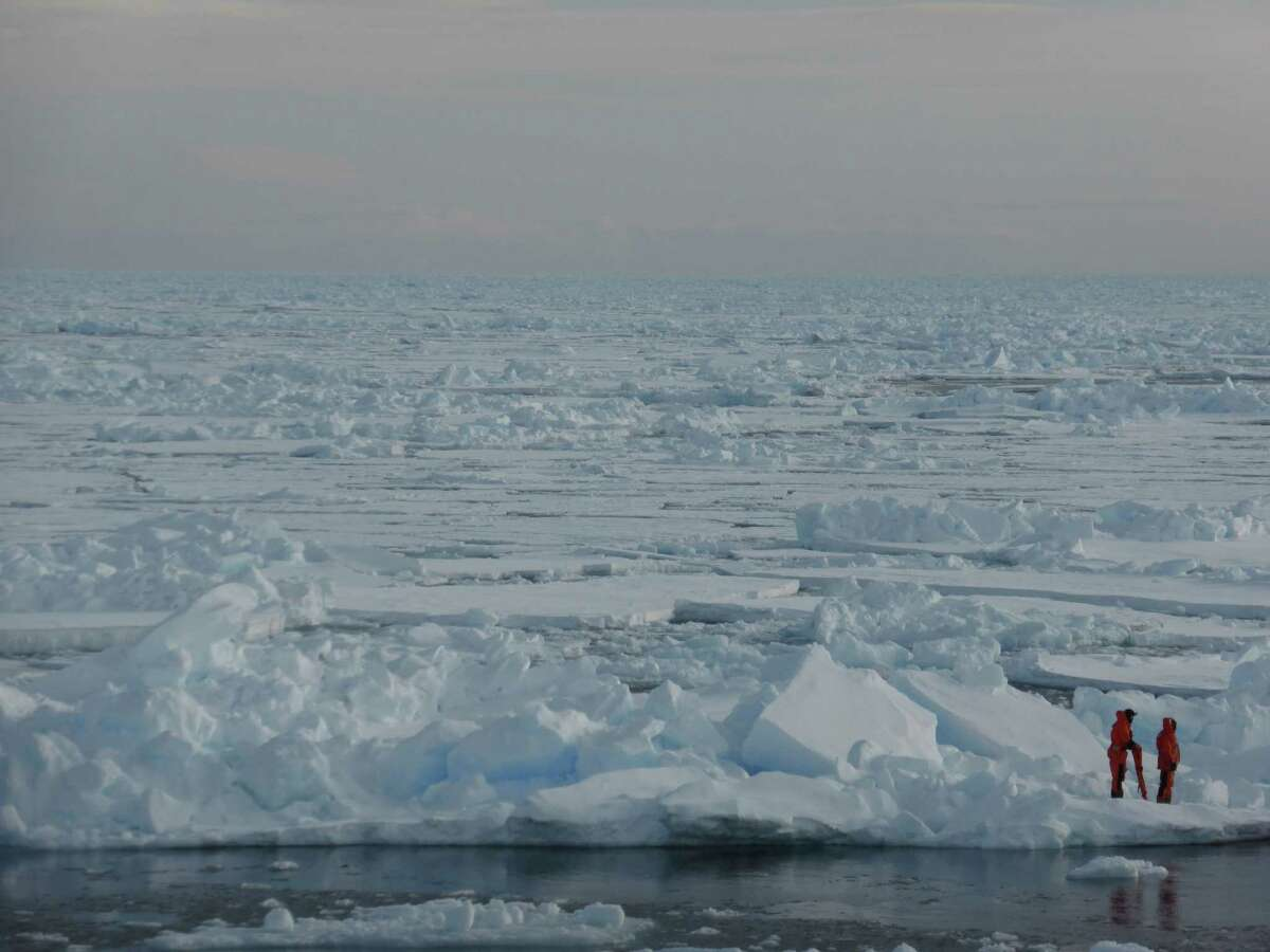 In this image provided by Dirk Notz, taken April 4, 2015, shows people waking on the ice in the Arctic near Svalbard, Norway. At current carbon emission levels, the Arctic will likely be free of sea ice in September around mid-century, which could make weather even more extreme and strand some polar animals, a study published Thursday in the journal Science finds. (Dirz Notz via AP)