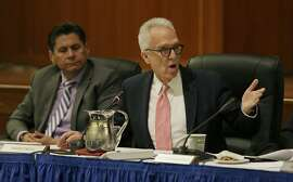 """File - In this March 23, 2016 file photo, Norman J. Pattiz, right, speaks as Eloy Ortiz Oakley, left, looks on during a University of California Board of Regents meeting in San Francisco. Regent Pattiz has apologized to a former employee for asking to hold her breasts while she taped a bra commercial. Pattiz said he """"deeply regrets"""" the comments and won't repeat such behavior. Pattiz is chairman of the Courtside Entertainment Group, which produces radio shows and podcasts. (AP Photo/Eric Risberg, File)"""