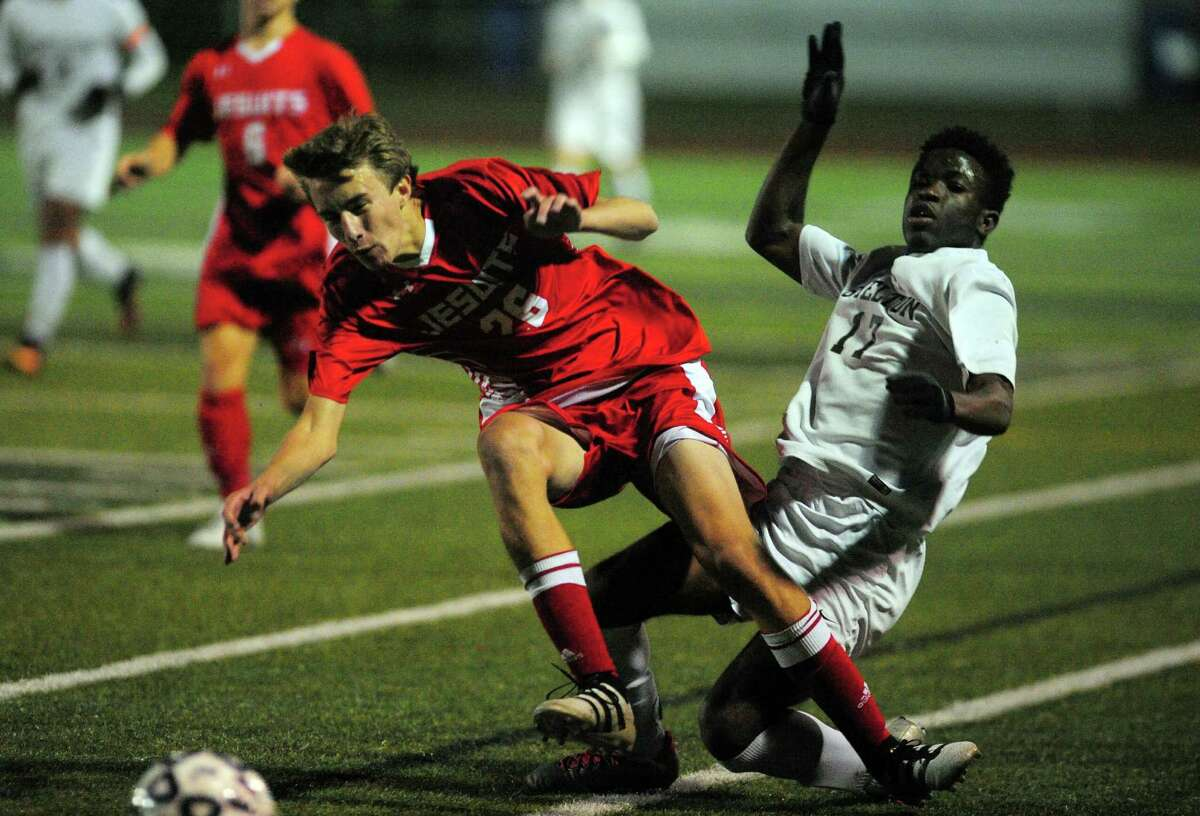 Fairfield Prep's Brian Donahue, left, and Shelton's Khaleed Dawkins collide while chasing the ball during SCC soccer championship action in West Haven, Conn. on Thursday Nov. 3, 2016.