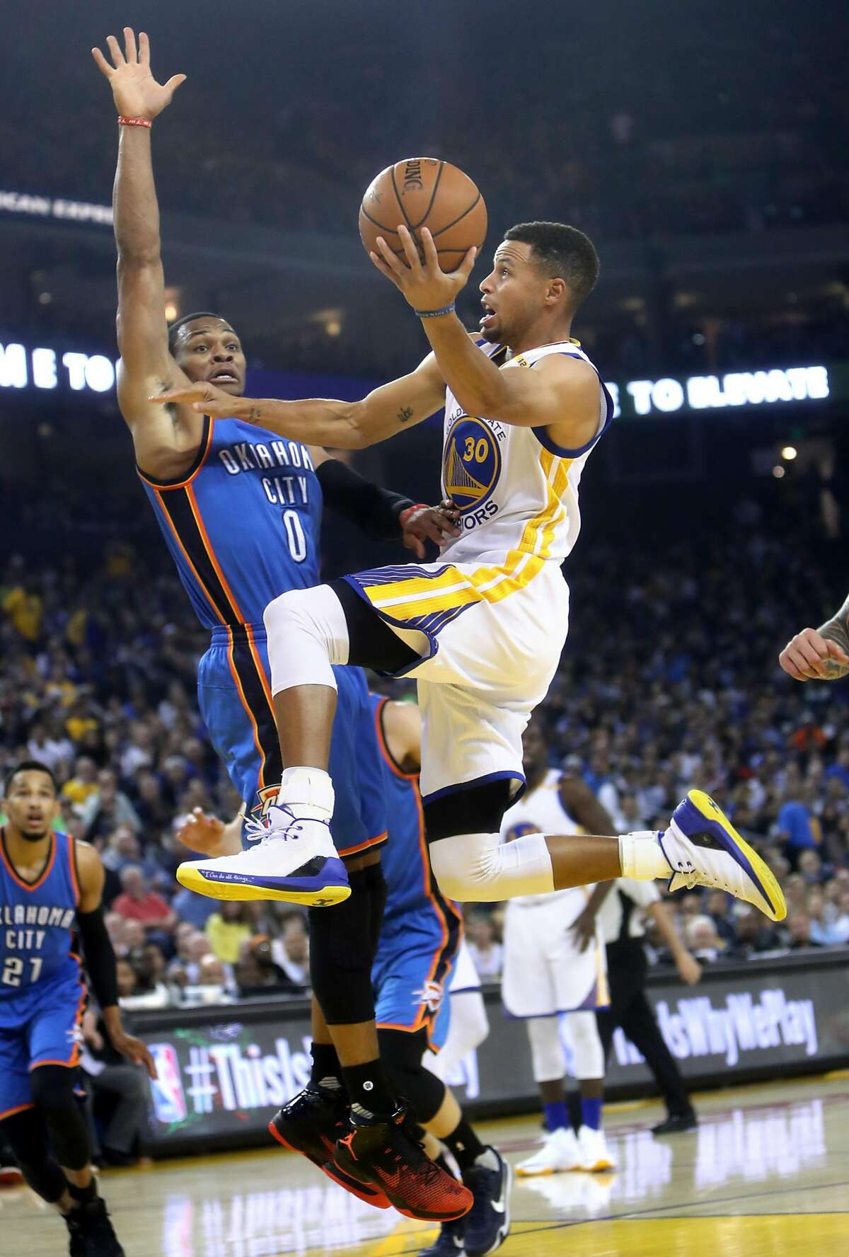 Golden State Warriors' Stephen Curry scores against Oklahoma City Thunder's Russell Westbrook in 1st quarter during NBA game at Oracle Arena in Oakland, Calif., on Thursday, November 3, 2016.