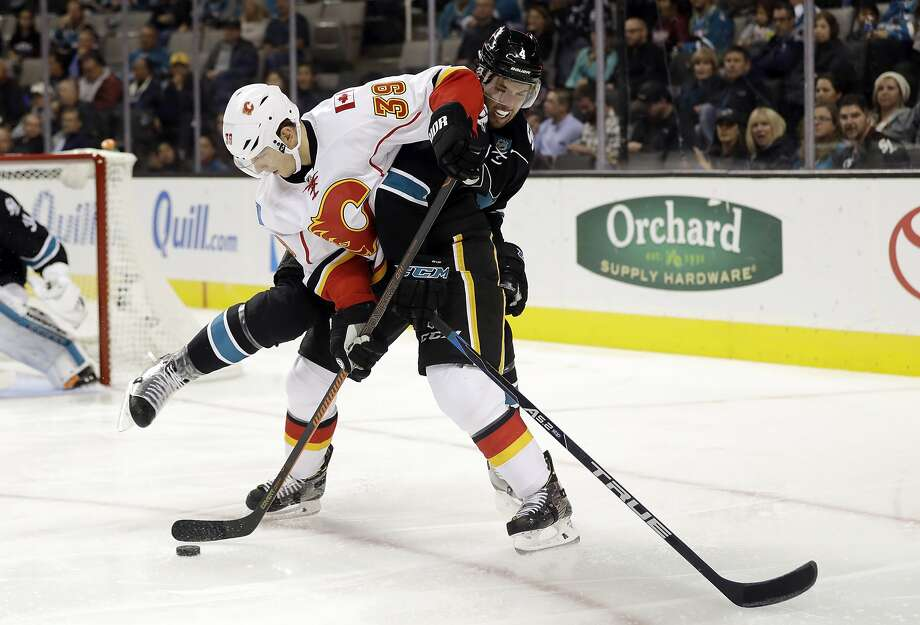 The Flames' Alex Chiasson (39) is defended by the Sharks' Brenden Dillon during the second period of San Jose's first home loss in five games at the Shark Tank. Both Sharks goals came in the third. Photo: Marcio Jose Sanchez, Associated Press