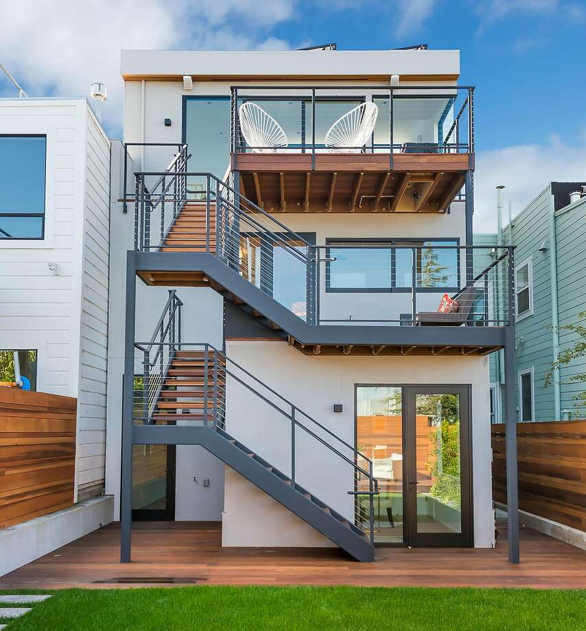 The trilevel home features outdoor spaces on all levels, as well as a wooden deck and level yard. Photo: Olga Soboleva / Vanguard Properties