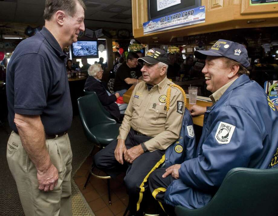 Ed Scheibel greets veterans (L-R) Bob Krokovich of Bethel and Luis Rosa of Danbury at Applebee's in Danbury on Veteran's Day in 2010, when the restaurant served up about 800 free meals. Photo: Scott Mullin / ST / The News-Times Freelance