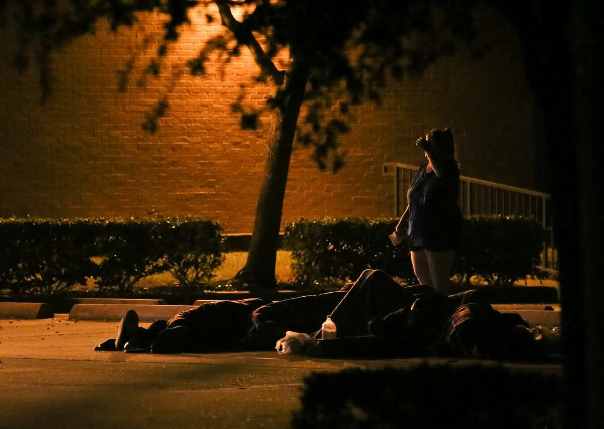 A group of people waits to be questioned by police at a scene in the 1200 block of Lovett, at the Charity Guild of Catholic Women, Friday, Nov. 4, 2016, in Houston.