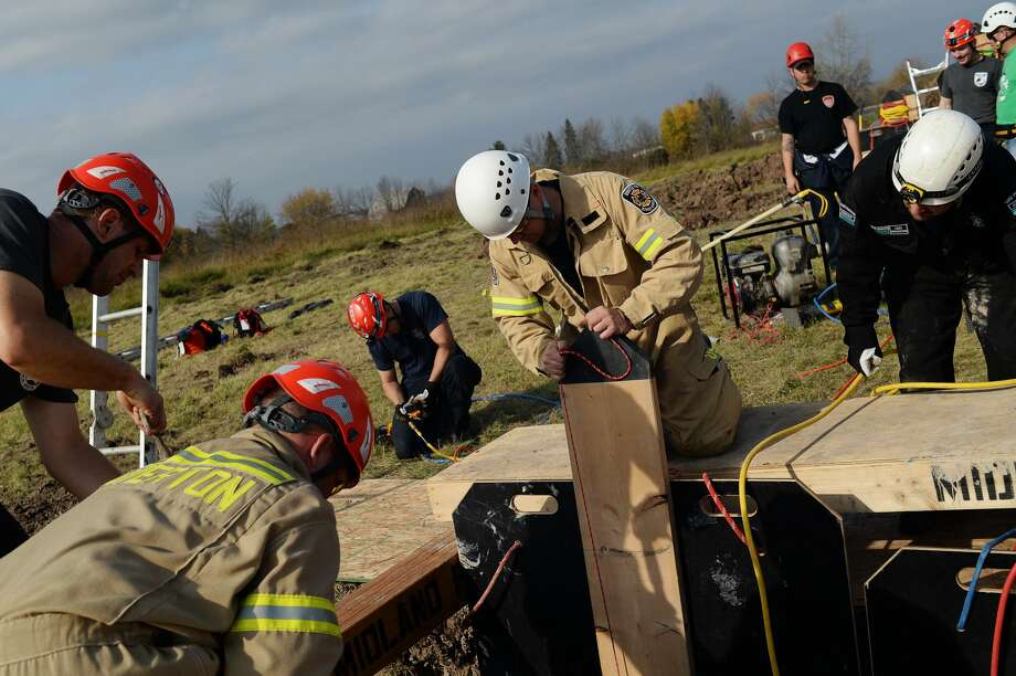Attendees secure panels to shore walls during trench rescue training organized by the Midland Fire Department on Tuesday afternoon at the Midland Landfill. Participants included firefighters from Bay, Gladwin and Saginaw counties, Dow Corning and Ontario. Photo: Erin Kirkland/Midland Daily News