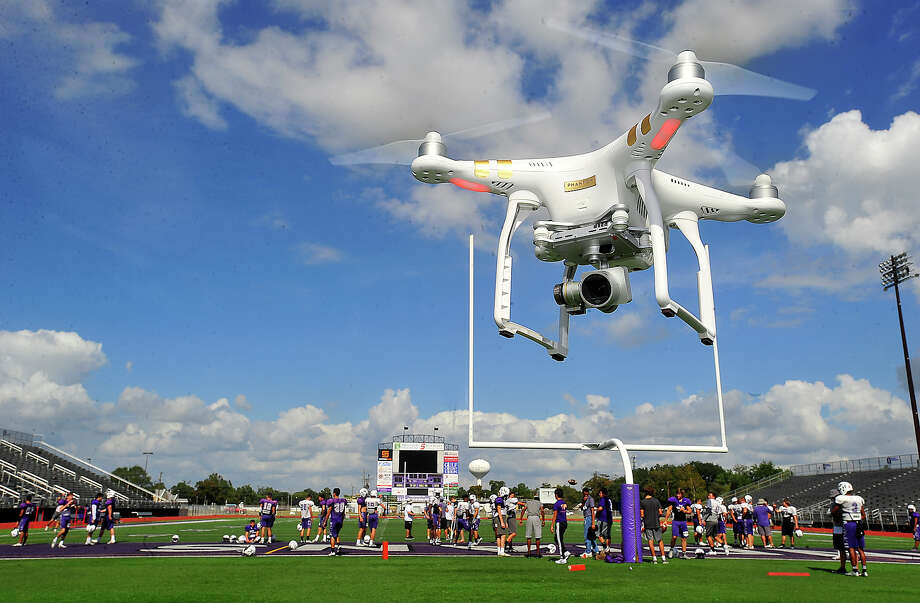 A drone powered by assistant coach Brian Cates hovers as Port Neches-Groves' varsity take the field for practice Thursday afternoon. While still not widely used by most high schools, drone footage is poised to be the next technological innovation embraced by coaches looking for new ways to elevate their game. Photo taken Thursday, November 3, 2016 Kim Brent/The Enterprise Photo: Kim Brent / Beaumont Enterprise