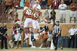 Andrew Beck (47) celebrates with TExas teammate Caleb Bluiett after scoring a touchdown on a 7-yard reception against the Baylor Bears during the second half on Oct. 29, 2016, in Austin.