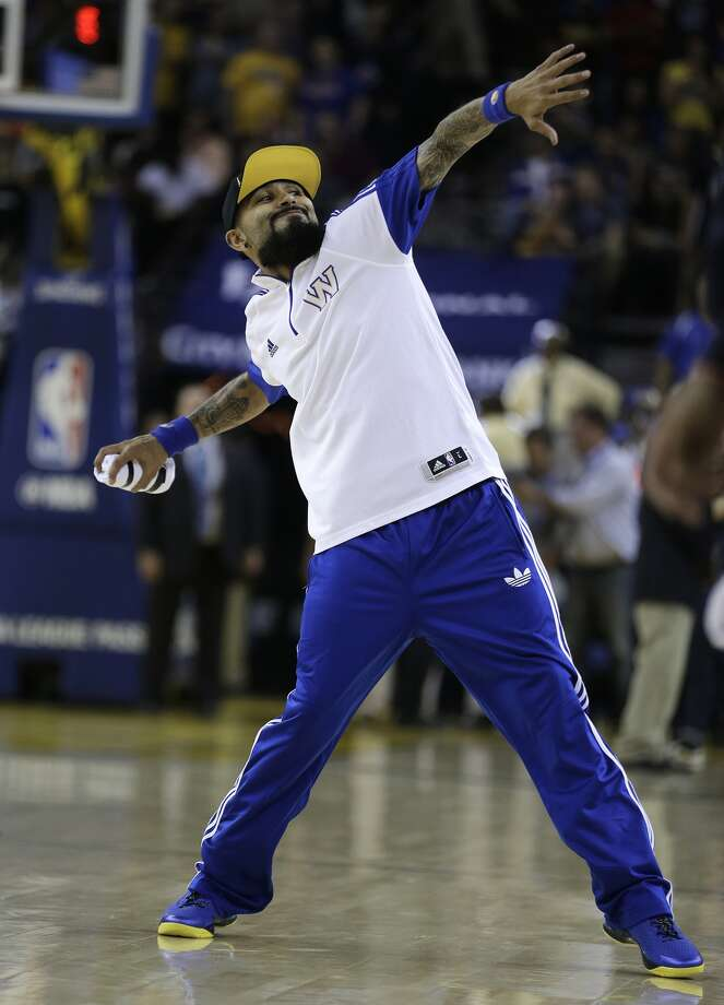 San Francisco Giants pitcher Sergio Romo throws a T-shirt during a timeout in the NBA basketball game between the Golden State Warriors and the Oklahoma City Thunder on Thursday, Nov. 3, 2016, in Oakland, Calif.