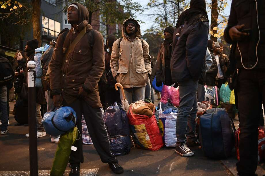 Refugees stand next to their belongings during a police evacuation of a makeshift camp near the Stalingrad metro station in Paris, one of several camps sprouting up around the French capital. Photo: LIONEL BONAVENTURE, AFP/Getty Images