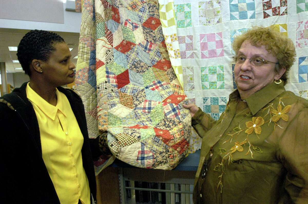 Alvin library clerk Cheryl Burse listens to librarian Danna K. Wilson talk about the different types of quilts on display at the Alvin Library.