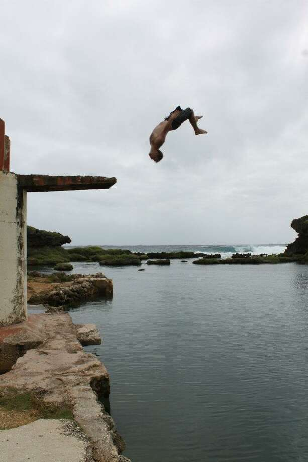 Brandon Rowlands, who had lived in Albany, flips while cliff diving in Guam in this undated photo. He died at 33 under questionable circumstances Oct. 25 in Costa Rica after serving a prison term and checking into a psychiatric hospital. (Photo courtesy of the Rowlands family)