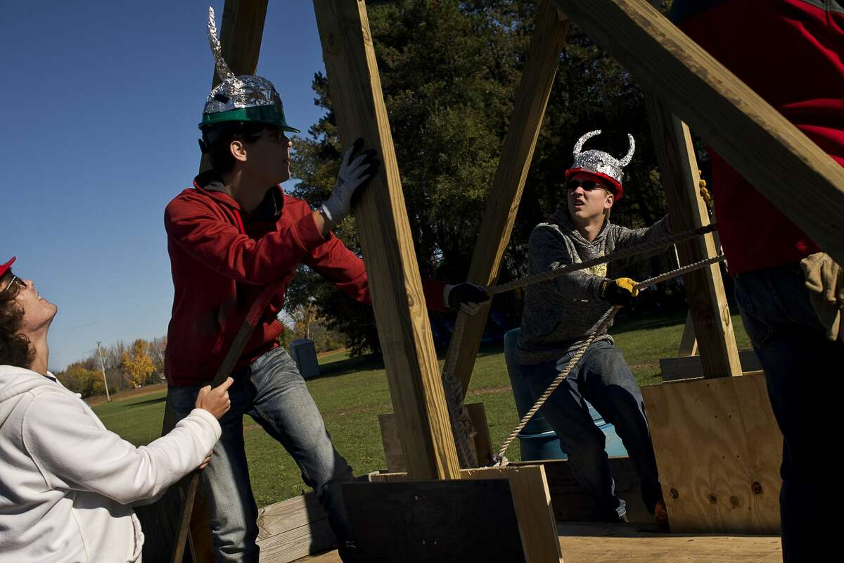 From left, Bullock Creek juniors and Masters of Medieval Destruction members Ethan Klopcic, 17, Austin Klopcic, 17, and Zach Leach, 16, prep their trebuchet on Friday at Bullock Creek's Annual Pumpkin Catapult Competition. Junior physics students designed and constructed trebuchets as part of their class work to see whose pumpkins would catapult the furthest.