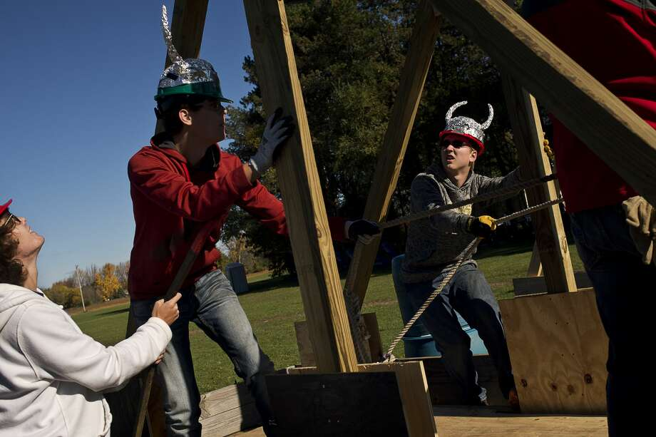 From left, Bullock Creek juniors and Masters of Medieval Destruction members Ethan Klopcic, 17, Austin Klopcic, 17, and Zach Leach, 16, prep their trebuchet on Friday at Bullock Creek's Annual Pumpkin Catapult Competition. Junior physics students designed and constructed trebuchets as part of their class work to see whose pumpkins would catapult the furthest. Photo: Erin Kirkland/Midland Daily News