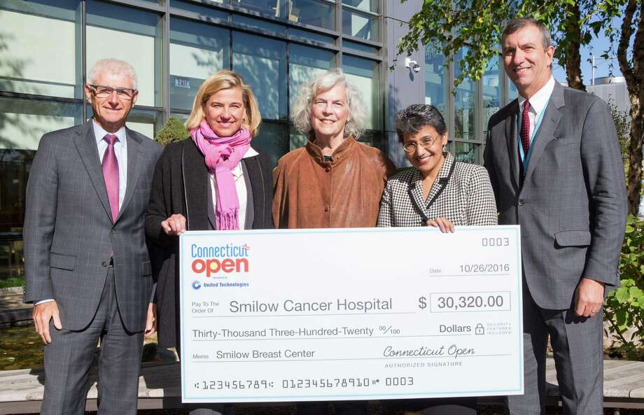 Tournament director Anne Worcester of New Canaan, second from left, presents a check for $30,320 to the Breast Center at Smilow Cancer Hospital at Yale New Haven. During the 2016 Connecticut Open, professional tennis players, local celebrities and fans participated in the Closer to Free Player Challenge by riding spin bikes. One hundred percent of the funds raised go directly to international breast cancer research at Smilow Cancer Hospital as a part of the Lion Heart Fund. Photo: Ray Paige / Contributed Photo / New Canaan News