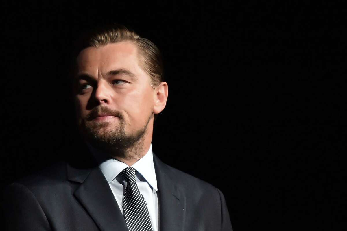 """US actor Leonardo DiCaprio looks on prior to speaking on stage during the Paris premiere of the documentary film """"Before the Flood"""" on October 17, 2016 at the Theatre du Chatelet in Paris. US actor Leonardo DiCaprio has issued an impassioned call for immediate action on climate change in """"Before the Flood"""", a documentary film making its premiere in Paris on October 17. DiCaprio takes viewers around the world to meet experts and politicians in order to reveal the scale of the problem, its effects and the paths towards solutions. / AFP PHOTO / POOL / CHRISTOPHE ARCHAMBAULTCHRISTOPHE ARCHAMBAULT/AFP/Getty Images"""