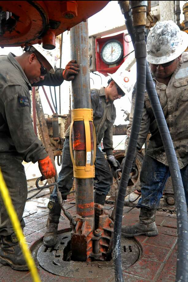 Floor hands put casing downhole on Trinidad Drilling Rig 433 on Wednesday, Nov. 2, 2016, in Midland County. James Durbin/Reporter-Telegram Photo: James Durbin