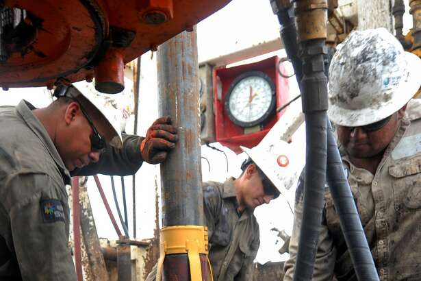 Floor hands put casing downhole on Trinidad Drilling Rig 433 on Wednesday, Nov. 2, 2016, in Midland County. James Durbin/Reporter-Telegram
