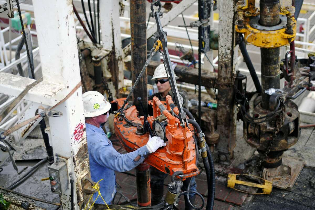 Kevin Giddings, left, and Noe Olvera, right, add a section of casing down a vertical well on the floor of Trinidad Rig 433 on Wednesday, Nov. 2, 2016, in Midland County. James Durbin/Reporter-Telegram