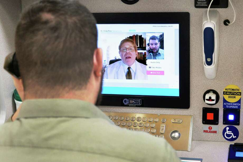 "Store pharmacist Michael Zappone, left, speaks with Dr. Craig Price of New Jersey during a demonstration of a new telemedicine option ""Doctor on Demand"" in New Jersey. The option in Texas is hampered by outdated regulations. Photo: John Carl D'Annibale /Albany Times Union / 10035204A"