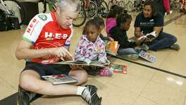 """Robert Alston (left) reads a book to Serenity Satterwhite, 3, as cyclists with Ride for Reading delivered books and provided tricycle safety tips to preschoolers at the Carroll Early Childhood Center. Approximately 40 volunteers from USAA and H-E-B participated in the organization's inaugural delivery in San Antonio, bringing 650 books to the children. """"We need to get books into the hands of children,"""" said Stephanie Ward, spokeswoman for the group."""