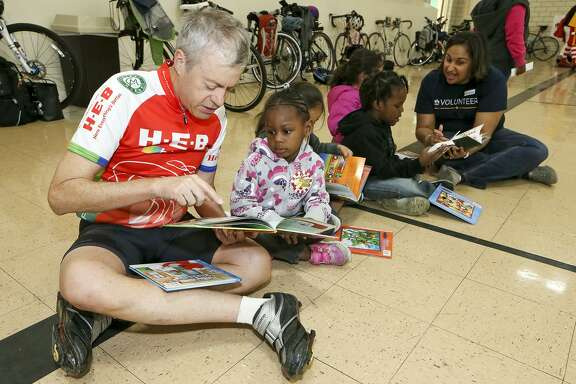 "Robert Alston (left) reads a book to Serenity Satterwhite, 3, as cyclists with Ride for Reading delivered books and provided tricycle safety tips to preschoolers at the Carroll Early Childhood Center. Approximately 40 volunteers from USAA and H-E-B participated in the organization's inaugural delivery in San Antonio, bringing 650 books to the children. ""We need to get books into the hands of children,"" said Stephanie Ward, spokeswoman for the group."