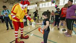 Ronald McDonald hands a Happy Meal Love Book to 4-year-old Faith Gonzales, as cyclists with Ride for Reading delivered books and provided tricycle safety tips to preschoolers at the Carroll Early Childhood Center. Approximately 40 volunteers from USAA and H.E.B participated in the organization's inaugural delivery in San Antonio, bringing 650 books to the children.