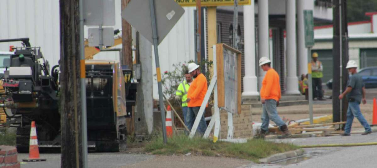 Construction workers inspect the damage caused to the gas line, which erupted at 2:30 p.m.