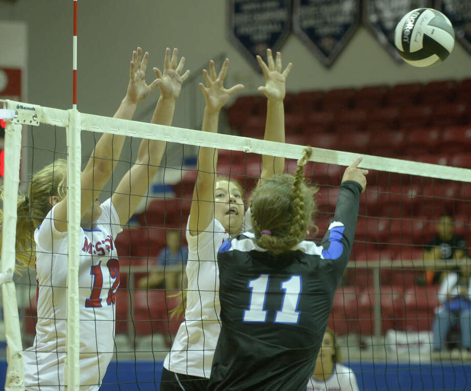 Midland Christian's Megan Ashton (12) and Lauren Danley (17) block a hit from Trinity's Mady Walker (11) on Tuesday, Aug. 9, 2016, at McGraw Events Center. James Durbin/Reporter-Telegram Photo: James Durbin