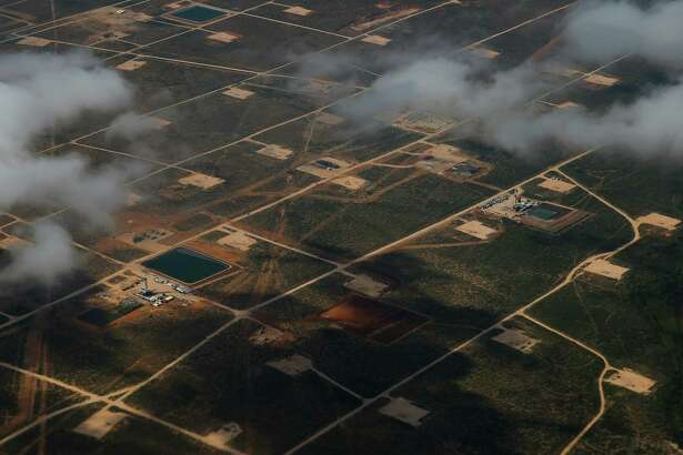 An aerial view of the Permian Basin outside of Midland shows the football field-size rectangles of land cleared by oil drillers.