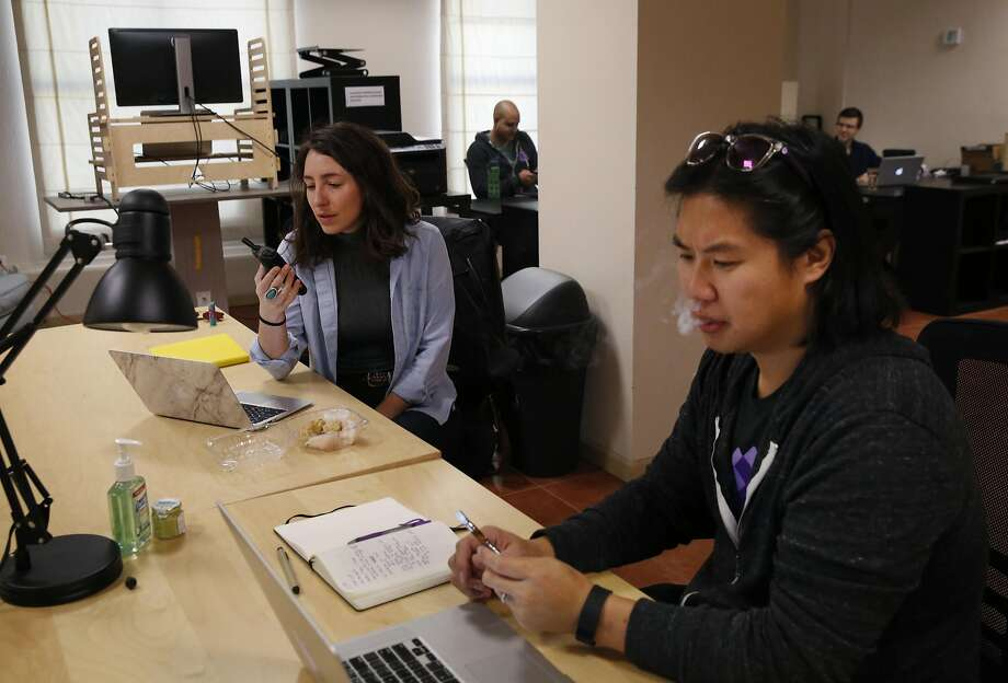 Sales director Cyo Nystrom (left) and CEO David Hua share a vaporizer with cannabidiol at Meadow Care in S.F., which permits marijuana use at work. Photo: Leah Millis, The Chronicle