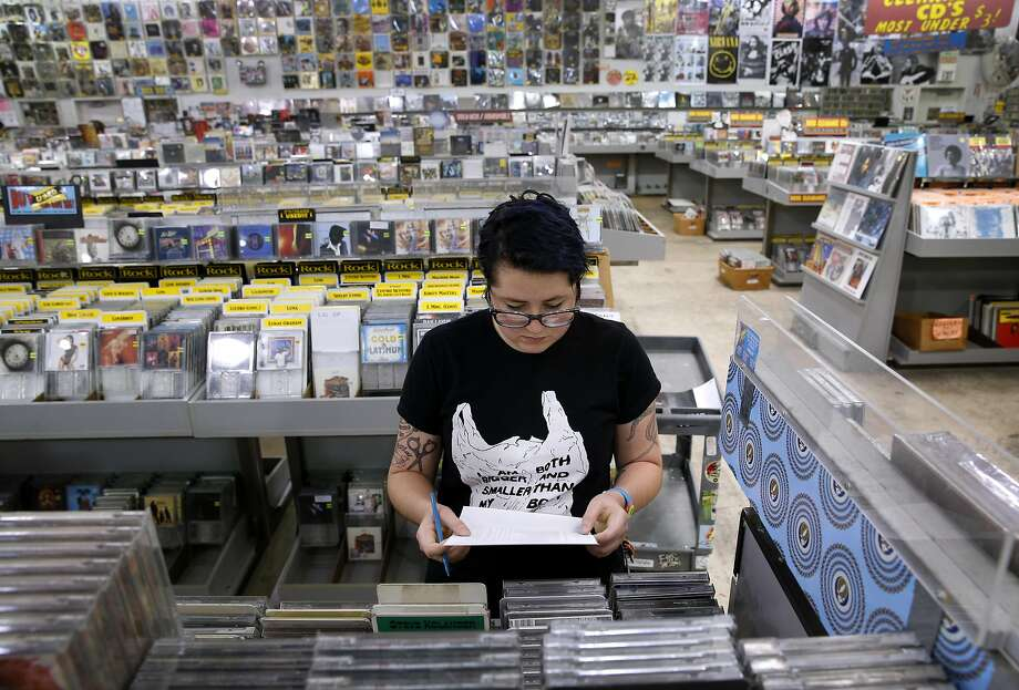 Employee Kiana Endres checks the inventory at the Amoeba music and record store on Haight Street in San Francisco, where a medical marijuana evaluation center is located on the second floor. Photo: Paul Chinn, The Chronicle