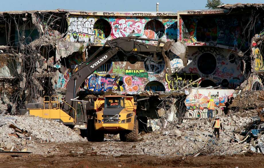 Workers demolish buildings on the western edge of Treasure Island, where a funding shortfall could delay the construction of crucial affordable housing. Photo: Michael Macor, The Chronicle