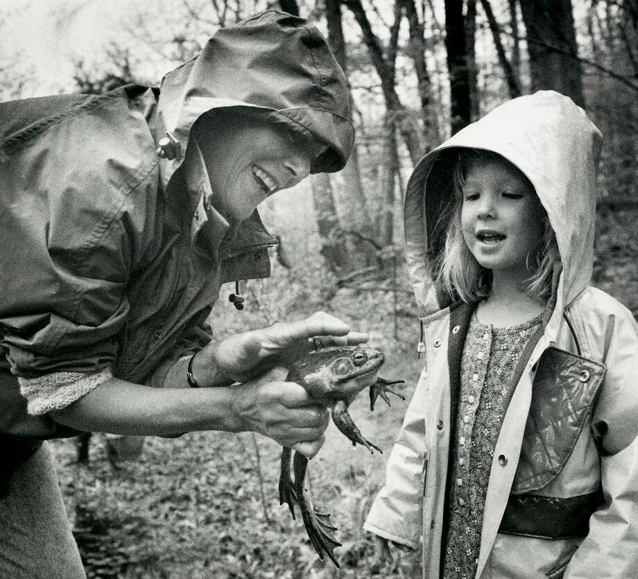 Georgie Ashforth, a volunteer teacher / naturalist at the Audubon Center in Greenwich displays a large male bull frog to Emily Smith of Rowayton in 1992. Indian Spring Pond was recently renamed in Ashforth's honor. Ashforth died in March. Photo: / GT