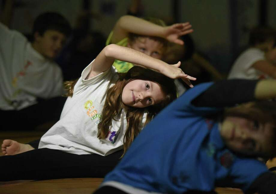 Anielka Breglia stretches with other students during the 10th annual third-grade ballet show at International School at Dundee in the Riverside section of Greenwich, Conn. Thursday, Nov. 3, 2016. In a partnership with Connecticut Ballet, ISD third-graders created their own ballet interpretation set to the plot of different classic stories. Photo: Tyler Sizemore / Hearst Connecticut Media / Greenwich Time