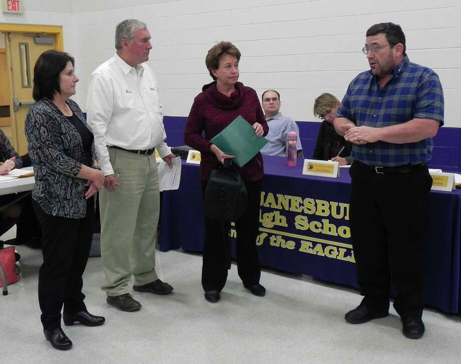 """Duanesburg Board of Education Vice President Kent Sanders, far right, accepts the Duanesburg Lions Club's donation of a Welch Allyn Spot Vision Screener for use at the elementary school, as Lions Jeannine Sanders, Stephen Perog and Cheryl Perog look on. """"It's important that children, especially preschoolers, are screened early, to catch amblyopia and other vision problems,"""" said Sanders, who is also a Duanesburg Lion. """"We appreciate having the use of the machine for our children."""" Attending the Lions Clubs International Convention in 1925, Helen Keller challenged Lions to become """"knights of the blind in the crusade against darkness."""" (Photo submitted)"""