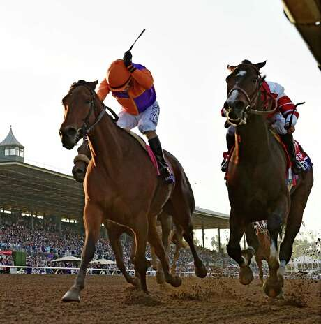 Jockey Gary Stevens, left, coaxes Beholder to the finish line ahead of Songbird and jockey Mike Smith for the victory in the Breeders' Cup Distaff on Friday. Photo: SKIP DICKSTEIN, Staff Photographer