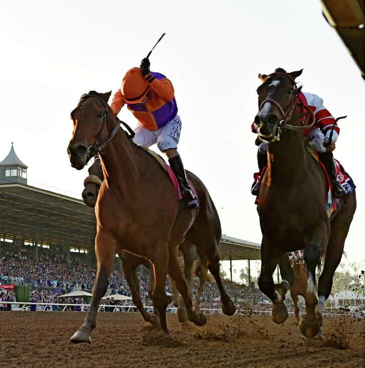 Jockey Gary Stevens, left, coaxes Beholder to the finish line ahead of Songbird and jockey Mike Smith for the victory in the Breeders' Cup Distaff on Friday.