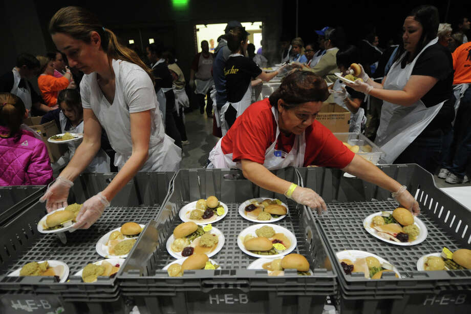 Jamie Shaw (left) and Silvia Villa (right), load trays with food during the 14th annual Feast of Sharing, a free turkey dinner for the community by H.E.B., Friday, Nov. 4, 2016, at Horseshoe Pavilion. James Durbin/Reporter-Telegram Photo: James Durbin