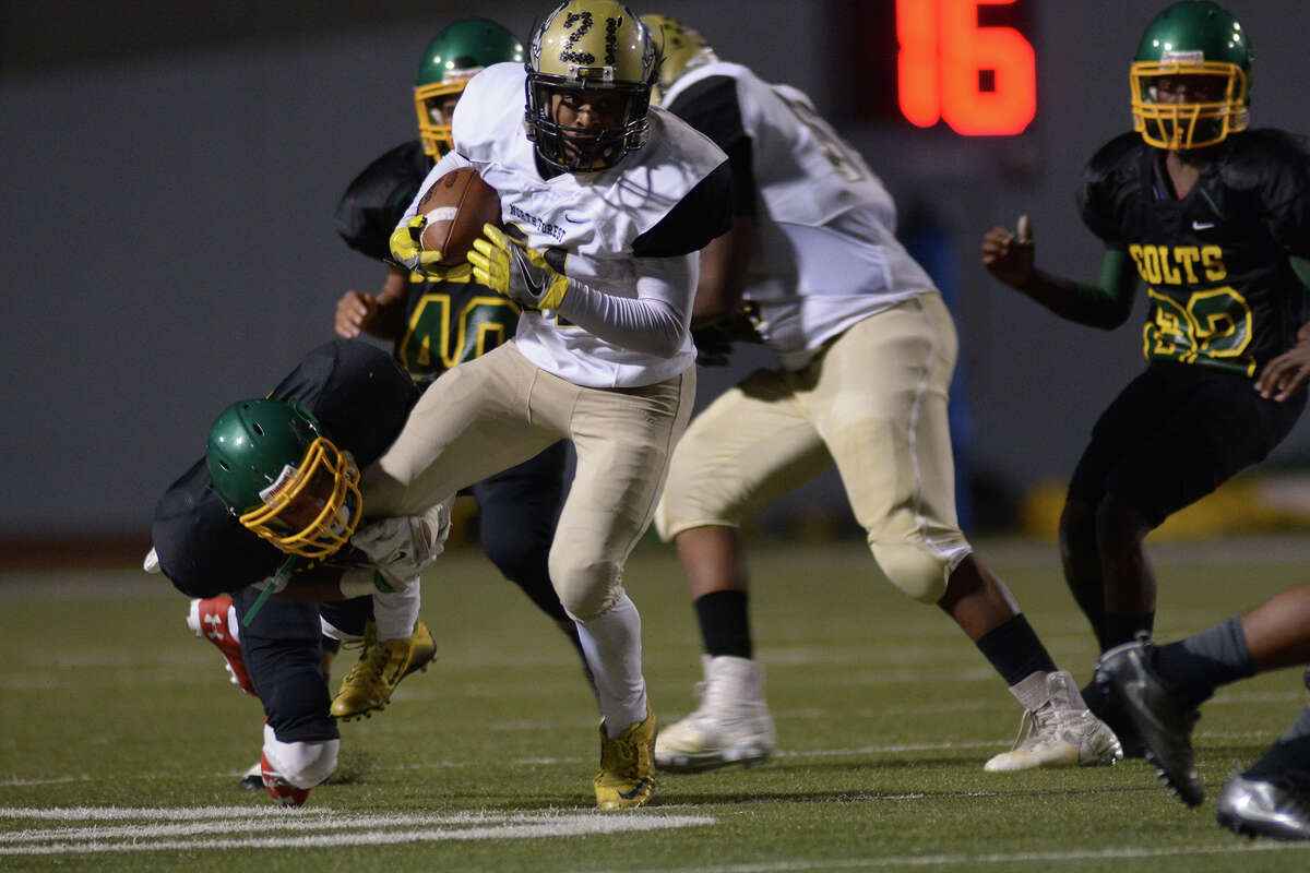 North Forest junior tailback Damond Wiggins (21) tries to break the grasp of Worthing senior defensive back Taurus Davis on a running play in the 2nd quarter of their district matchup at Barnett Stadium on Friday, Nov. 4, 2016. (Photo by Jerry Baker/Freelance)