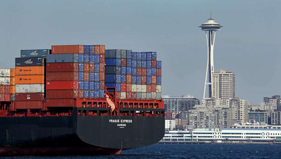 FILE - In this Feb. 15, 2015 file photo, the Space Needle towers in the background beyond a container ship anchored in Elliott Bay near downtown Seattle.  The U.S. trade deficit fell in September 2016 to the lowest level in 19 months as demand for U.S.-made airplanes and other exports increased while imports slipped. The politically sensitive deficit with China declined. (AP Photo/Elaine Thompson, File) Photo: Elaine Thompson, STF / Copyright 2016 The Associated Press. All rights reserved.
