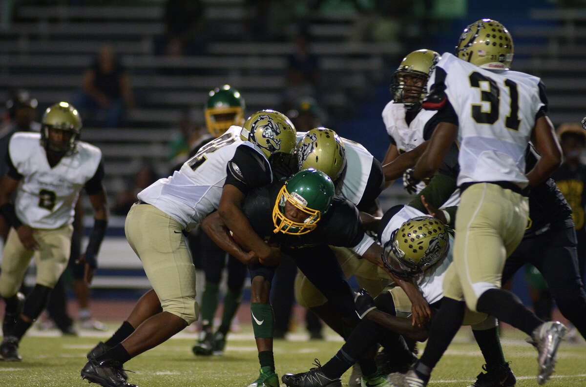 North Forest defenders Mark Smith, left, and Rufus Wade, bottom right, team up on a tackle of Worthing senior quarterback Deeago Thomas, center, during the the 2nd quarter of their district matchup at Barnett Stadium on Friday, Nov. 4, 2016. (Photo by Jerry Baker/Freelance)
