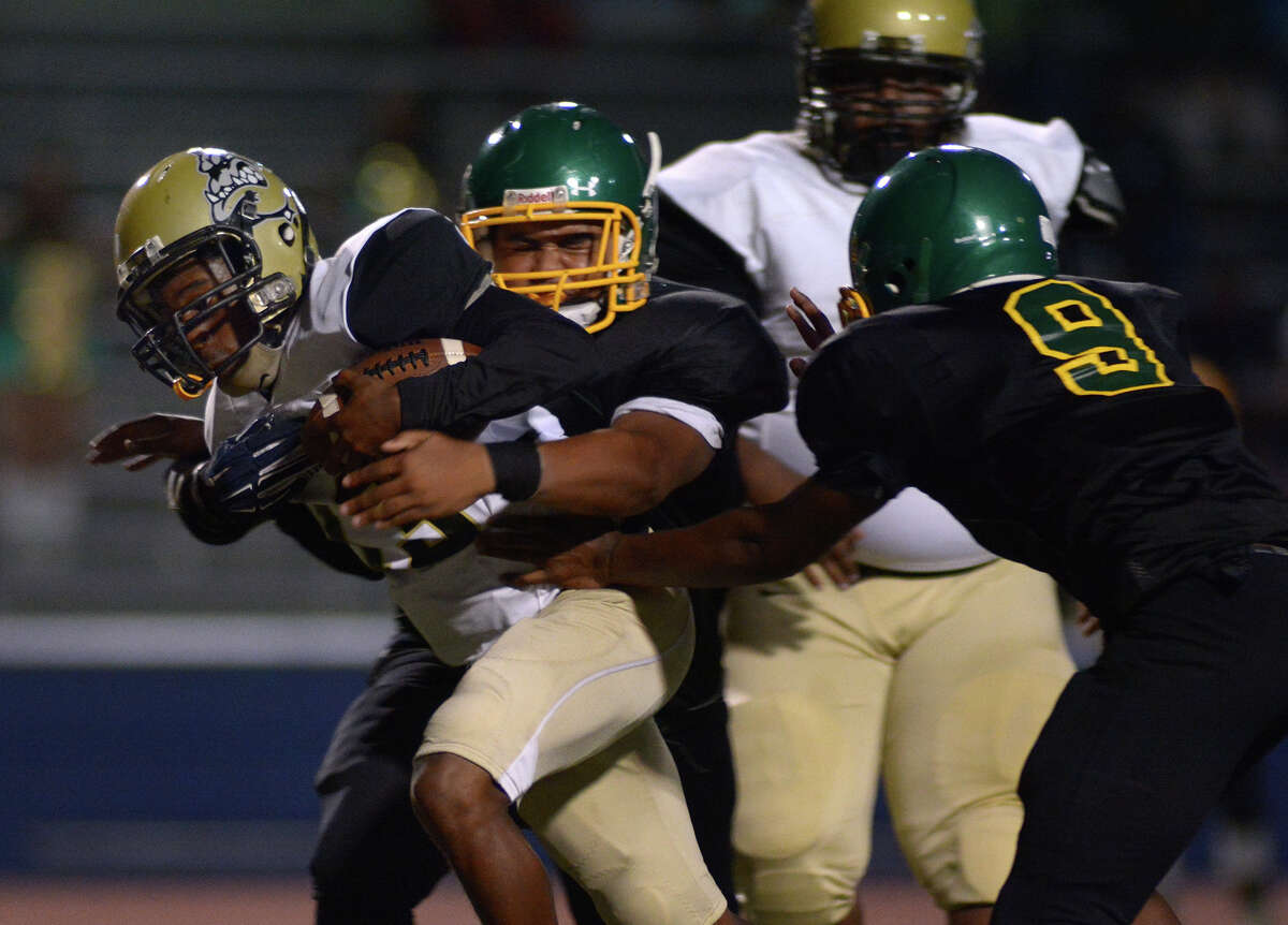 North Forest senior quarterback Rashand Jones, left, tries to break free of Worthing sophomore defensive tackle Trey Cotton near the goal line on a running play in the 1st quarter of their district matchup at Barnett Stadium on Friday, Nov. 4, 2016. (Photo by Jerry Baker/Freelance)