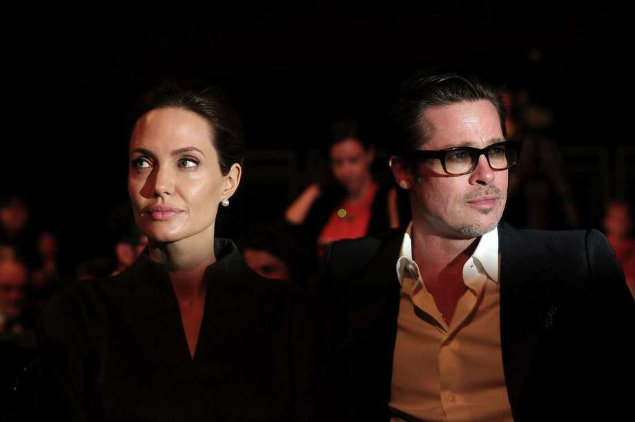 (FILES) This file photo taken on June 13, 2014 shows US actress and special UN envoy Angelina Jolie (L) and her husband US actor Brad Pitt attending the fourth day of the Global Summit to End Sexual Violence in Conflict in London. US actress Angelina Jolie has filed for divorce from her husband Brad Pitt after two years of marriage and 12 years together, announced on September 20, 2016 by the website TMZ celebrity. / AFP PHOTO / Carl COURTCARL COURT/AFP/Getty Images ORG XMIT: 1456 Photo: CARL COURT / AFP or licensors